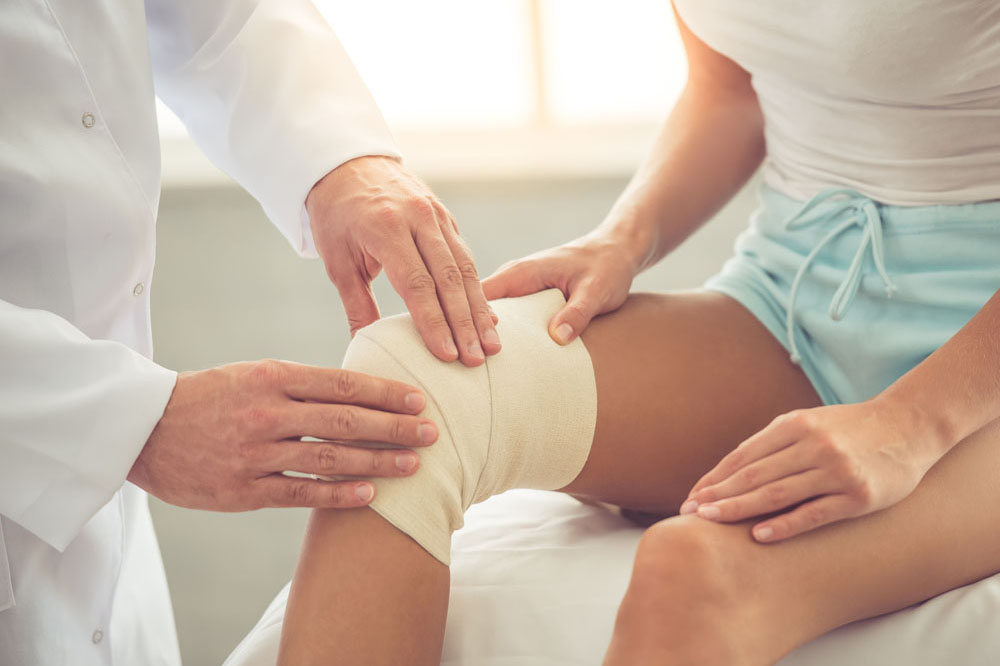 Cropped image of handsome doctor bandaging woman's injured knee while working in his office