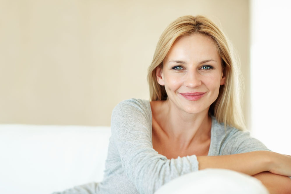 Closeup of beautiful middle aged woman relaxing on couch at home